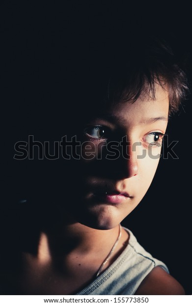 sad boy in the dark, focused light on the one side, toned image