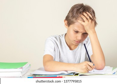 Sad boy doing homework. Education, school, learning difficulties concept