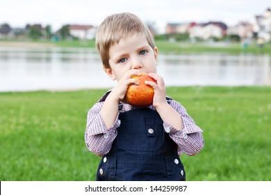 Sad boy eats an apple on the lawn