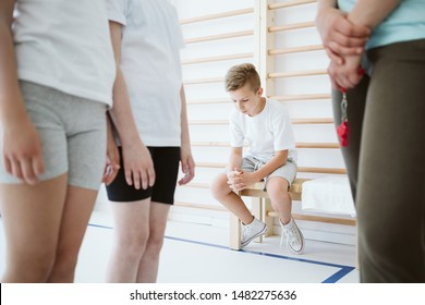 Sad boy excluded from the group during physical education