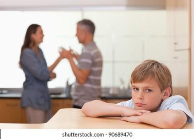 Sad boy hearing his parents having am argument in a kitchen