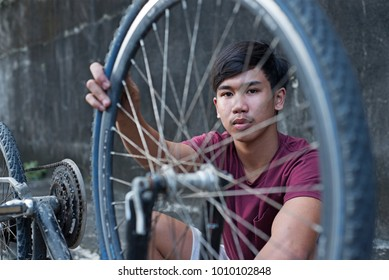 Sad boy holding an old bicycle tire.