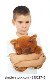 Sad boy holding teddy bear isolated on white background