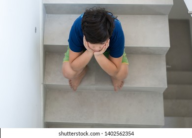 Sad boy in home on stairs