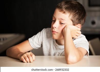 Sad boy at home. Unhappy child. Emotions stress at teenager