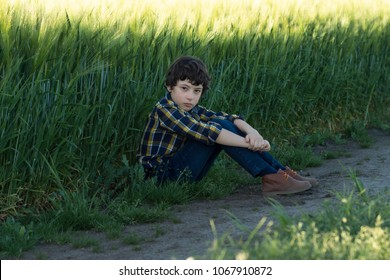 A sad boy in jeans and a shirt is sitting in the field.