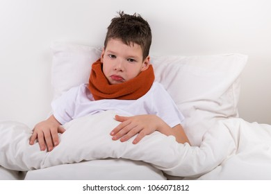 sad boy lies on the bed, neck is rewound with a warm scarf