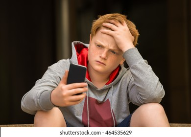 Sad Boy Looking At Mobile Phone With Hand On Head