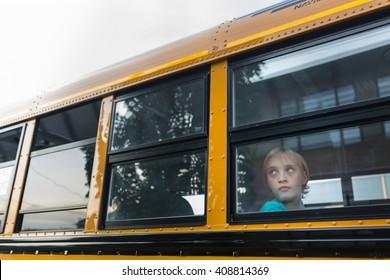 Sad boy looking out school bus window