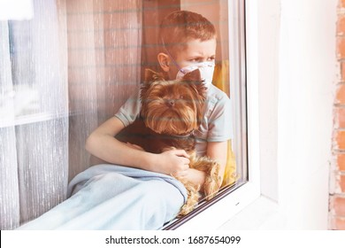 Sad boy in medical mask with his dog sits on windowsill and looks out window, self quarantine. View from street. Patient isolated to prevent infection of coronavirus, Covid-19 epidemic, pandemic.