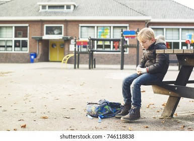 sad boy outside at schoolyard