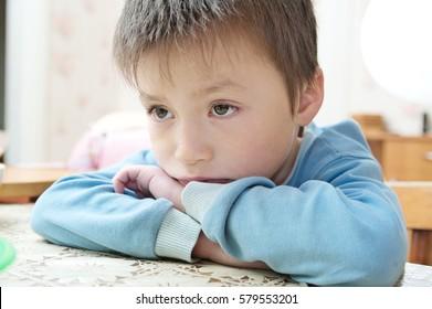 Sad boy portrait looking away thinking sitting on the table, thoughtful child feeling hurt