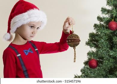 Sad boy in Santa cap looking at xmas toy near Christmas tree