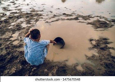 Sad boy scooping water from the lake ,drought and global warming.