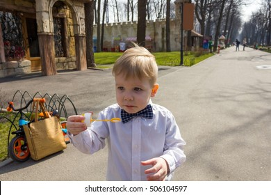 Sad boy in shirt is playing with bubbles