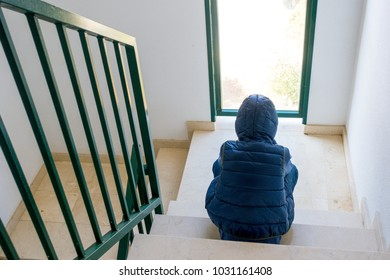 Sad boy sitting alone in the corner of a staircase