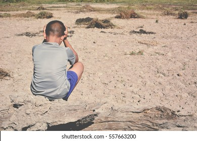 Sad a boy sitting on dry ground .concept hope and drought