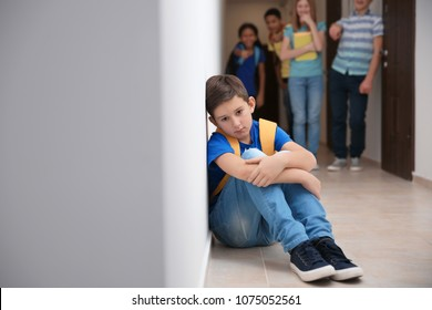 Sad boy sitting on floor indoors. Bullying in school
