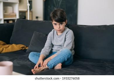 sad boy sitting on a sofa in living room