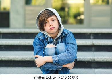 Trauriger Junge sitzt auf der Treppe, vor der Schule. Allein unglückliches Kind in der Stadtstraße. Mobbing, Depression, Kinderschutz oder Einsamkeit Konzept. Depressiver Jugendlicher.
