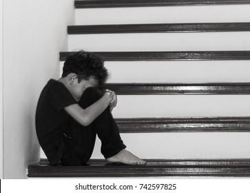 Sad boy is sitting on the stairs, sad boy