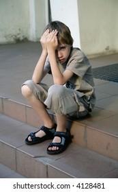 sad boy sitting on steps
