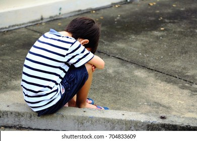A sad boy is sitting on the street alone. Unhappy lonely child.