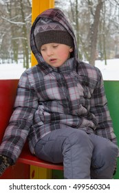sad boy sitting in the park winter