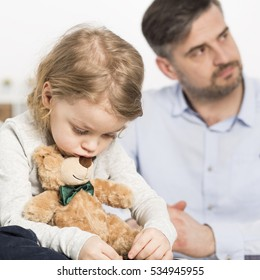 Sad boy sitting with teddy bear with angry father in the back