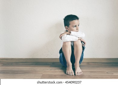sad boy thinking,boy sitting on the floor of the room against the wall, his expression is very unfortunate and sad