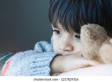 Sad boy wearing knit jumper cuddle teddy bear sitting next to window,Lonely kid with sad face,Child playing with brown bear and looking out with thinking face, Toddler hugging teddy