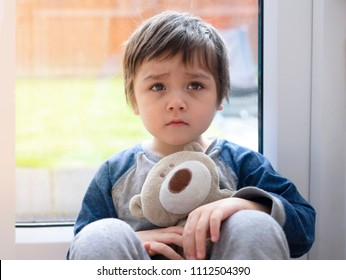 Sad boy wearing pajamas cuddle teddy bear sitting next to glass door with sun light in the morning,Lonely kid with sad face,Scared child waking up because of bad dream,Toddler hugging teddy