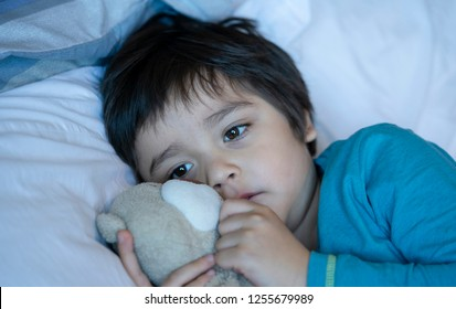 Sad boy wearing pajamas cuddle teddy bear in bed on the morning, Sad kid waking up from nightmare, Scared child waking up early morning because of bad dream, Toddler hugging teddy