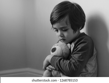 Sad boy wearing pyjamas cuddle teddy bear sitting at corner in the morning, Lonely kid looking dow with sad face, Scared child waking up because of bad dream,Toddler hugging teddy