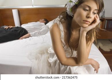 Sad bride with groom asleep in background