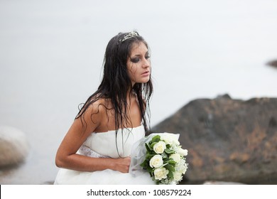 Sad bride sitting on the sea-shore and crying in the rain