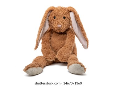 Sad brown teddy rabbit, soft toy in child's bedroom with colorful books