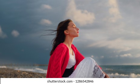 Sad brunette girl in red cardigan alone on empty seashore in cloudy weather.