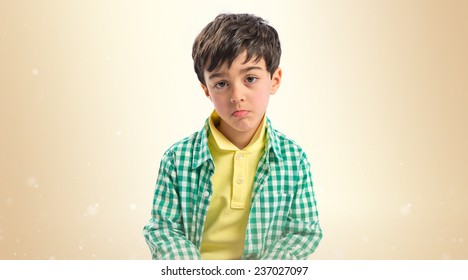 Sad brunette kid over ocher background
