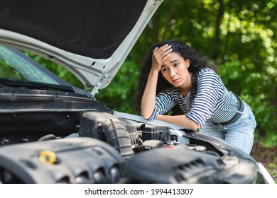 Sad brunette woman leaning on car hood, experiencing broken engine while car trip, waiting for auto service, closeup. Depressed young lady having troubles with her car, waiting for help