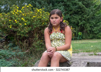 Sad bullied fat gypsy child girl in dress sitting alone on stairs in garden unhappy
