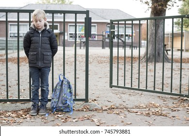 sad bullied kid. No friends, standing alone at the school gate.