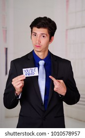 Sad business man holding a paper of you're fired text on it, in a blurred background