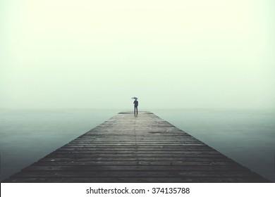 Sad business man with umbrella looking at the horizon