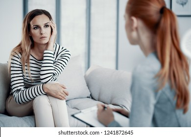 Sad business woman consulting psychiatrist about her eating disorder problems during session in office.