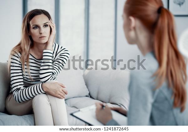 Triste mujer de negocios consultando a un psiquiatra sobre sus problemas de desorden alimenticio durante la sesión en el cargo.
