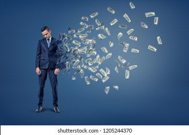 A sad businessman with head hanging down starts to deteriorate with his body turning into flying banknotes. Losing your fortune. Selling yourself for money. Money maker.