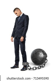 A sad businessman looks down while shackled to a large iron ball with a chain to his ankle. Boundaries and troubles. No way ahead. Bureaucracy limits.