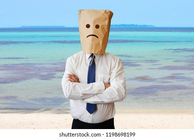 Sad businessman on the beach