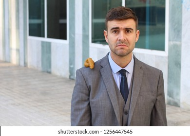 Sad businessman with poop on his shoulder